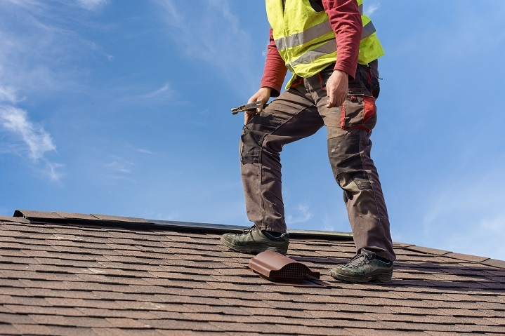 roofer replaces tile blown off by wind