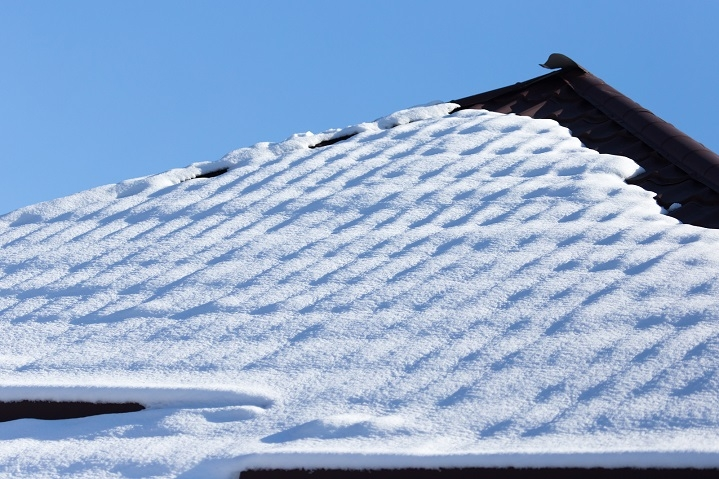Snow on pitched roof of house.