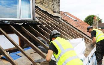 Two men stripping a roof of its tiles and protective membrane