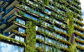 A skyscraper with plants growing on window ledges and balconies to reduce pollution