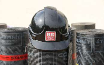 A black RG Leverett Ltd helmet resting on roofing materials